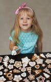 Litet barn som dekorerar kakor med isläggning Arkivfoto