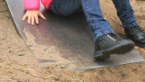 Litet barn som flyttar sig ner på en stålglidbana utomhus lager videofilmer