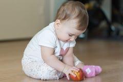 Litet barn som hemma sitter på golvet med ett rött äpple Arkivfoton