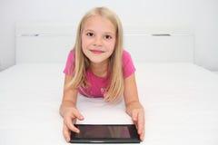 Litet barn som hemma spelar med minnestavlan, bärbara datorn och telefonen Arkivfoton