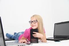 Litet barn som hemma spelar med minnestavlan, bärbara datorn och telefonen Royaltyfri Foto