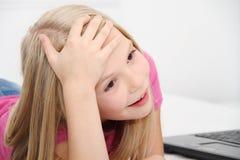 Litet barn som hemma spelar med minnestavlan, bärbara datorn och telefonen Fotografering för Bildbyråer