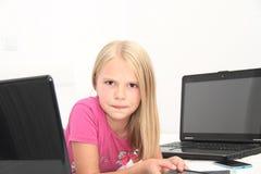 Litet barn som hemma spelar med minnestavlan, bärbara datorn och telefonen Arkivbild