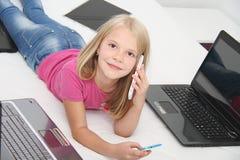 Litet barn som hemma spelar med minnestavlan, bärbara datorn och telefonen Arkivfoto
