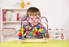 Litet barn som leker med en utmana toy Arkivfoton