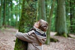 Litet barn som omfamnar trädstammen Arkivbild