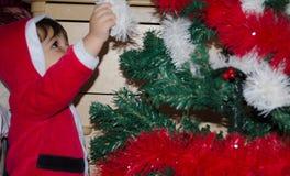 Litet barn som sätter julgarnering på julträd royaltyfri fotografi