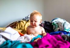 Litet barn som sitter i hög av tvätterit på säng royaltyfri bild