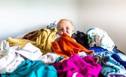 Litet barn som sitter i hög av tvätterit på säng royaltyfria foton