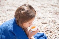 Litet barn som slås in i den blåa handduken som dricker kopp te på den utomhus- sommarstranden Royaltyfri Fotografi