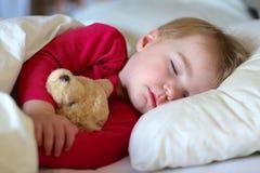 Litet barn som sover i säng Arkivfoto