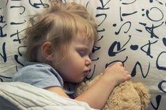 Litet barn som sover med nallebjörnen royaltyfri bild