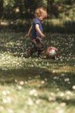 Litet barn som sparkar bollen Arkivbilder