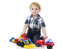 Litet barn som spelar bilar och lastbilar Arkivbilder