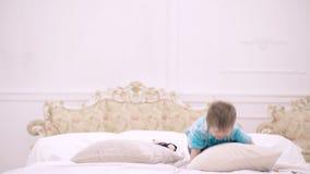 Litet barn som spelar i säng, hem- fritid Lycklig pojke som hoppar på sängen Begrepp av lycklig barndom sömntid till stock video