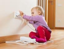 Litet barn som spelar med elektrisk förlängning Royaltyfri Foto