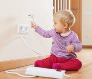 Litet barn som spelar med elektrisk förlängning Fotografering för Bildbyråer