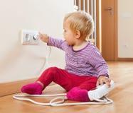 Litet barn som spelar med förlängningskabel och elektriskt uttag Arkivbild