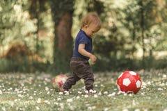 Litet barn som spelar med fotboll i gräset Royaltyfri Bild