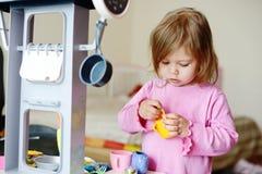 Litet barn som spelar med kök Arkivbilder