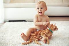 Litet barn som spelar med katten Arkivbilder
