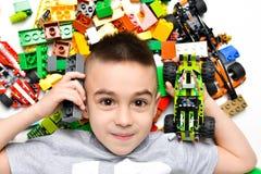 Litet barn som spelar med massor av f?rgrika plast- leksaker inomhus och att bygga olika bilar och objekt arkivfoton