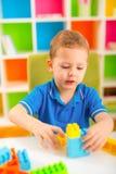 Litet barn som spelar med massor av inomhus färgrika plast- kvarter Arkivfoton