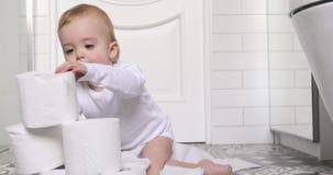 Litet barn som spelar med sammanträde för toalettpapper på golv lager videofilmer