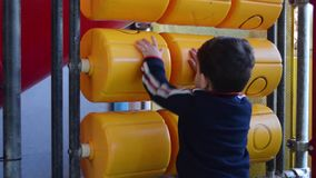 Litet barn som spelar med snurr x och tidig utveckling för oxebräde lager videofilmer