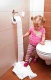 Litet barn som spelar med toalettpapper Arkivfoton