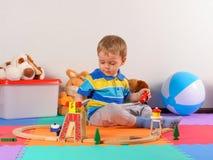 Litet barn som spelar med träjärnvägen Royaltyfria Bilder