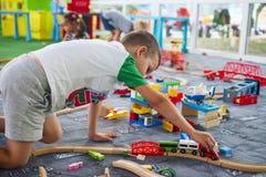 Litet barn som spelar med träjärnvägen på golvet Pys som spelar med trädrevuppsättningen royaltyfri fotografi