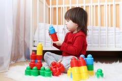 Litet barn som spelar plast- kvarter Royaltyfri Foto