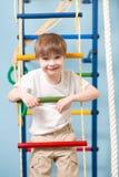 Litet barn som spelar sportar på sportmitten Ungepojkeanseende på en repstege fotografering för bildbyråer