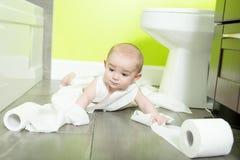 Litet barn som upp river sönder toalettpapper i badrum fotografering för bildbyråer
