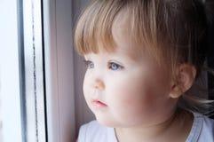 Litet barn som ut ser fönstret behandla som ett barn flickan som önskar att gå utomhus på regnigt väder arkivfoton