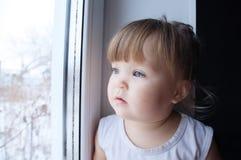 Litet barn som ut ser fönstret behandla som ett barn flickan som önskar att gå utomhus på regnigt väder arkivfoto