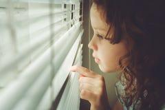 Litet barn som ut ser fönstret till och med rullgardinerna Royaltyfri Bild