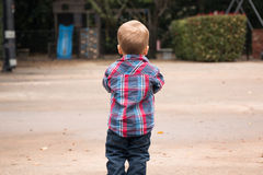 Litet barn som utanför vänder mot i väg från kameran Royaltyfri Foto