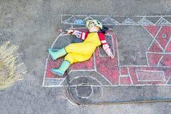 Litet barnbarn av fyra år som har gyckel med bild D för brandlastbil Arkivbild