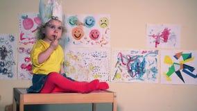 Litet barnbarn med den pappers- kronan som äter kakor som sitter på den lilla tabellen arkivfilmer