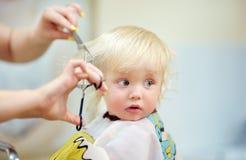 Litet barnbarn som får hans första frisyr Royaltyfri Fotografi