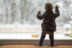 Litet barnbarn som framme står av en stor fönsterbenägenhet mot arkivfoton