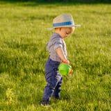 Litet barnbarn utomhus Årig en behandla som ett barn den bärande sugrörhatten för pojken som använder att bevattna kan Arkivfoto