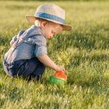 Litet barnbarn utomhus Årig en behandla som ett barn den bärande sugrörhatten för pojken som använder att bevattna kan Arkivbilder