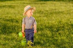 Litet barnbarn utomhus Årig en behandla som ett barn den bärande sugrörhatten för pojken som använder att bevattna kan Royaltyfri Foto