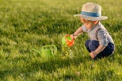 Litet barnbarn utomhus Årig en behandla som ett barn den bärande sugrörhatten för pojken som använder att bevattna kan Arkivbild