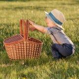 Litet barnbarn utomhus Årig en behandla som ett barn den bärande sugrörhatten för pojken som ser i picknickkorg Arkivbilder
