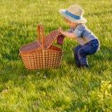 Litet barnbarn utomhus Årig en behandla som ett barn den bärande sugrörhatten för pojken som ser i picknickkorg Arkivfoto
