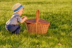 Litet barnbarn utomhus Årig en behandla som ett barn den bärande sugrörhatten för pojken som ser i picknickkorg Fotografering för Bildbyråer